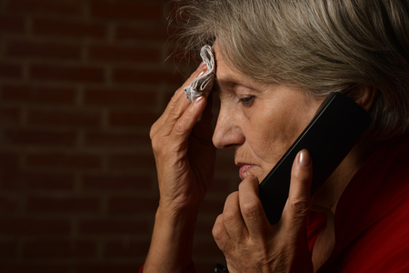sick person: Older sick woman in red is speaking on phone on a background of a brick