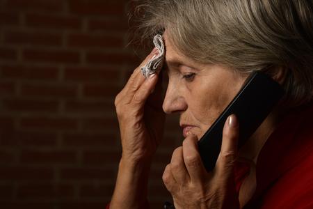 persona enferma: Una más vieja mujer enferma en rojo está hablando en el teléfono sobre un fondo de un ladrillo Foto de archivo