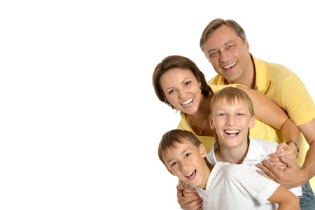 family indoors: Happy family of four standing on white background