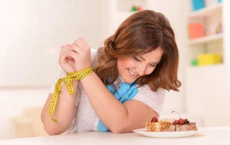 persona deprimida: Mujer de dieta feliz con la torta y cinta métrica Foto de archivo