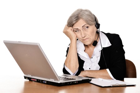 computer user: Old sad woman with a laptop on a white background