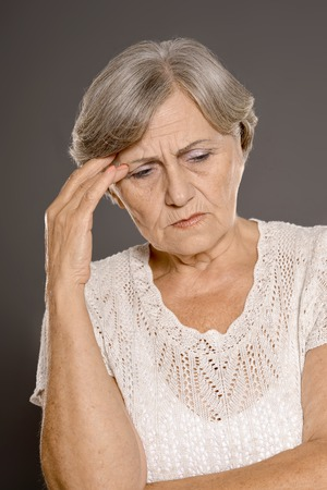 lamentable: Portrait of an older woman with a headache on a gray background