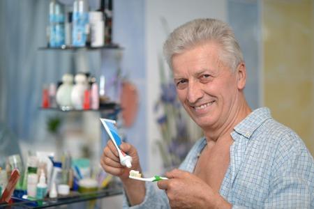 Cute aged guy brushing his teeth in bathroom