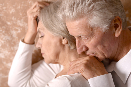 lamentable: Close-up portrait of a sad elder couple on brown background