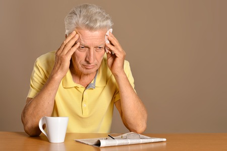 lamentable: Portrait of older man sitting at table Stock Photo