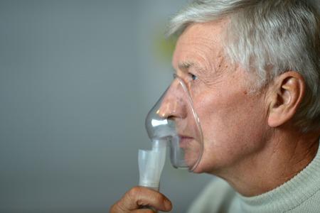 inhalation: Close-up portrait of an elder man making inhalation