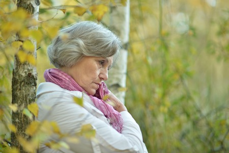 sad old woman: Niza anciana triste en el fondo del oto�o Foto de archivo
