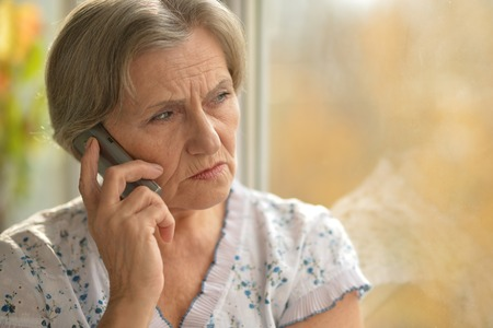 sick person: Sick elderly woman calling on phone at home Stock Photo