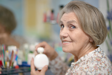 50 60 years: Senior woman applying cream in front of a mirror Stock Photo
