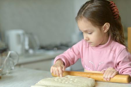 little dough: Little girl kneading dough at the kitchen Stock Photo