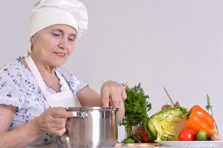 cheerful grandma is preparing dinner for the whole family photo