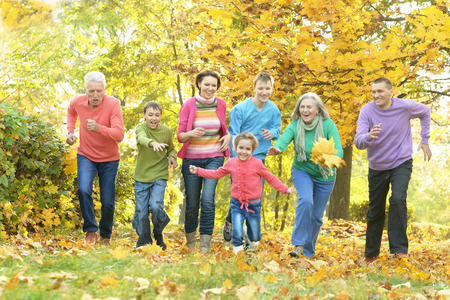 fall leaves: Happy smiling family relaxing in autumn park Stock Photo