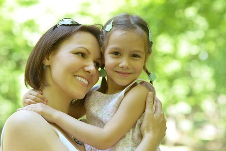 commercial tree care: Happy mother with her daughter walk in summer park Stock Photo