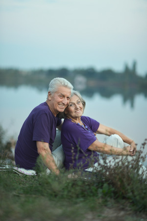 Portrait of a happy mature couple sitting near lake photo