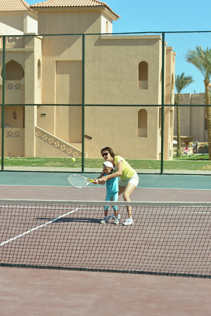 Little girl and her mother playing tennis photo