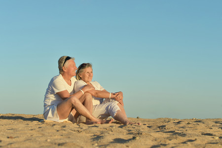 Happy Mature couple sitting on beach against the sky photo