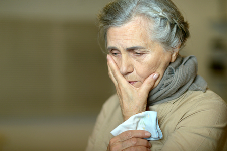 an elderly person: Portrait of a cute sad aged woman