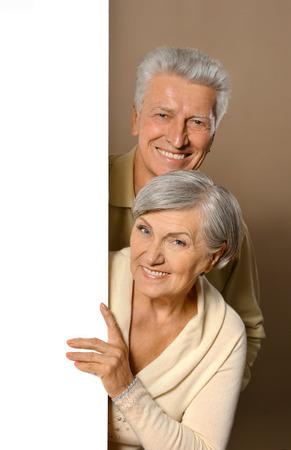 Portrait of an elderly couple  posing with board Standard-Bild