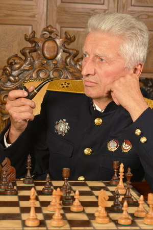 colonel: Military mature general at the table playing chess