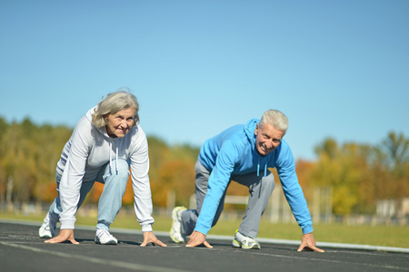 grandparents: Happy fit senior couple jogging at stadium