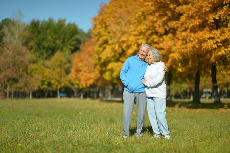 old people walking: Happy elderly couple walking in autumn park