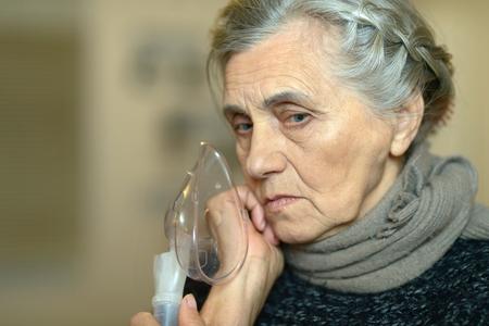 inhalation: Senior woman making inhalation on dark background
