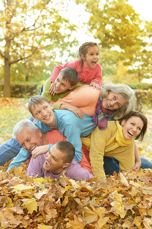 Happy smiling family relaxing in autumn park Standard-Bild
