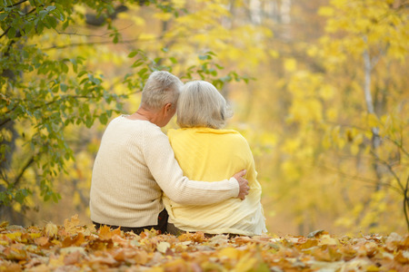 Happy senior couple relaxing in autumn park back