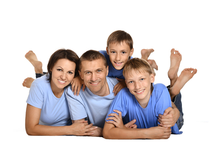 happy family of three people lying on the floor on a white background photo