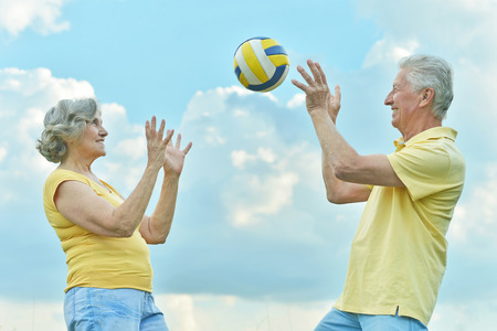 elderly couple playing volleyball against the sky Standard-Bild