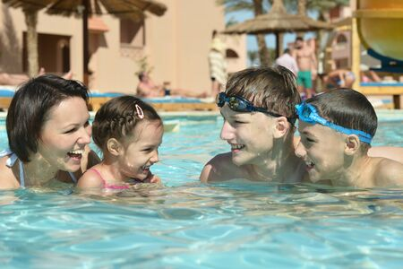 Portrait of a happy family having fun in pool photo