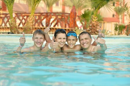 Happy family having fun in pool with thumbs up photo