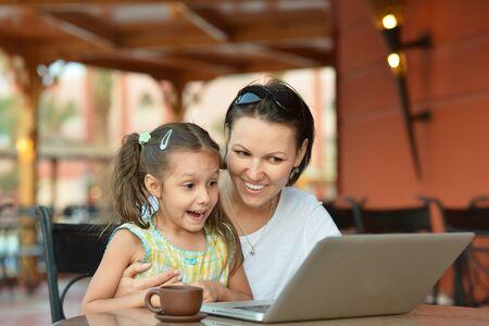 madre trabajando: Mujer joven con chica equipo port�til