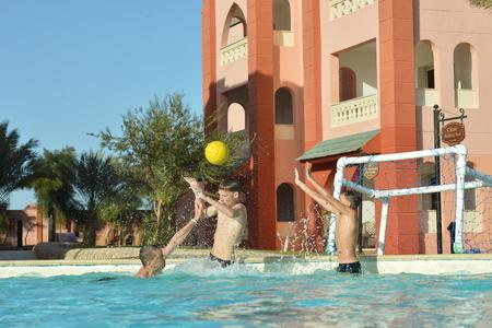 waterpolo: Padre e hijos jugando waterpolo en la piscina Foto de archivo