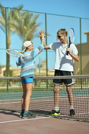 brothers playing: Dos hermanos activos que juegan en la pista de tenis
