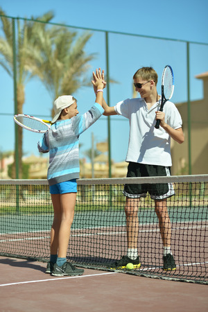 argue kid: Two active brothers playing at tennis court