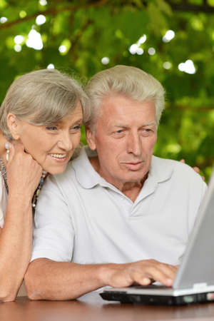 Happy senior couple sitting in summer at table with laptop photo