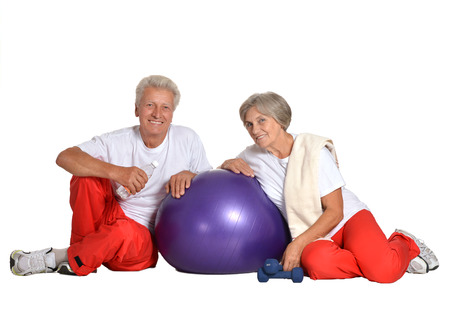 european people: Elderly couple exercising,sitting on a floor of a gym isolated on white
