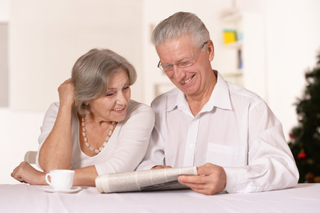 Portrait of amusing old couple reading newspaper