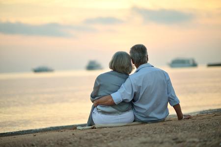 mujeres mayores: Feliz pareja madura que se relaja en la playa al atardecer, vista posterior
