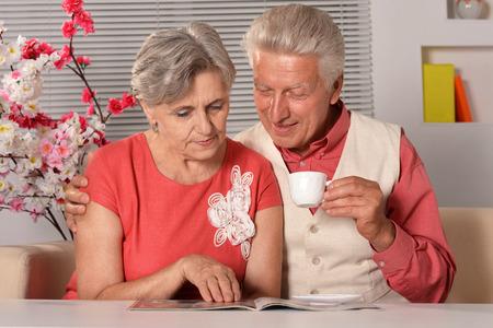 Portrait of senior couple reading magazine at home photo