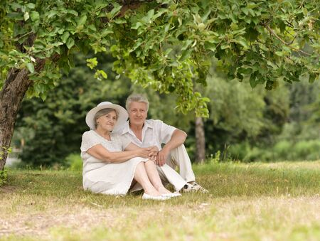 Happy elderly couple sitting in autumn nature photo