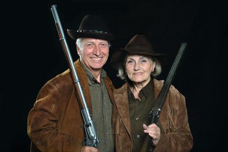 stickup: Happy Gunslingers in western garment on black Stock Photo