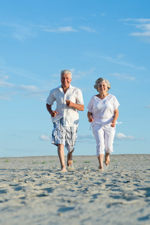 Old couple running on a beach in a sunny day Standard-Bild