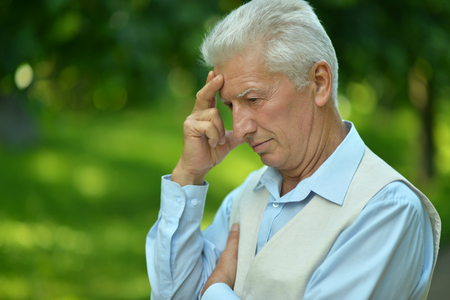 man think: Serious senior man thinking in park on green background Stock Photo