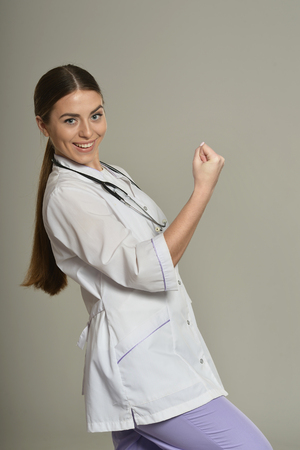 victory symbol: Female doctor gesturing victory symbol on grey background Stock Photo
