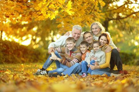 幸せな秋の公園で坐っている家族の笑顔