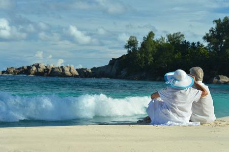 damas antiguas: Pareja de ancianos sentados en la orilla y se ve en el mar Foto de archivo