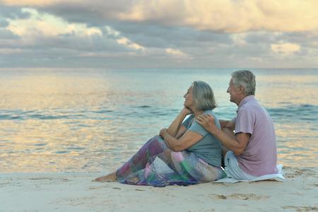 mujeres ancianas: Pareja de ancianos sentados en la orilla y se ve en el mar Foto de archivo