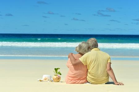 personas sentadas: Pareja de ancianos sentados en la orilla y se ve en el mar Foto de archivo